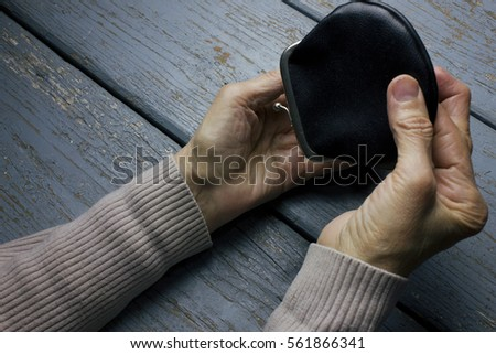 old woman opened the purse to count money #561866341