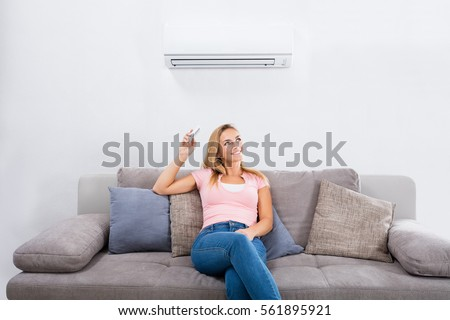 Young Happy Woman Sitting On Couch Operating Air Conditioner With Remote Control At Home #561895921
