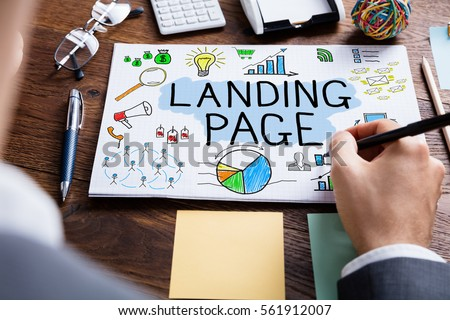High Angle View Of Businessperson Drawing Landing Page Concept At Wooden Desk  Royalty-Free Stock Photo #561912007