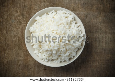 Bowl of organic rice on wooden table #561927334
