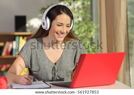 Beautiful portrait of a student learning on line watching video tutorials with a red laptop and headphones in a table at home Royalty-Free Stock Photo #561927853