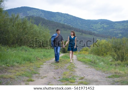 Lovers man and woman walking on a rural road. A date in nature. #561971452