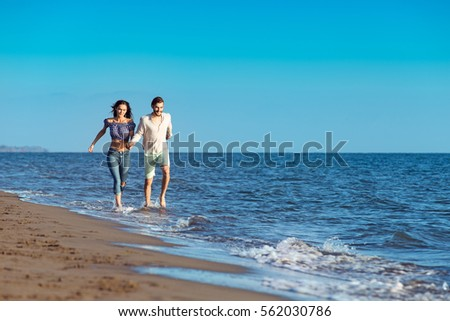 happy couple running on the beach #562030786