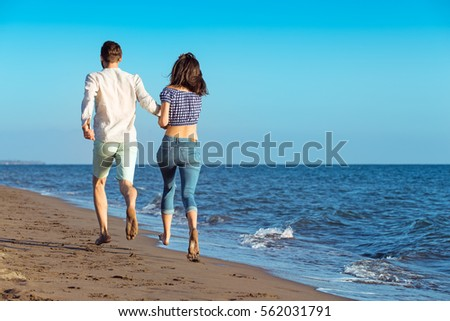 happy couple running on the beach #562031791