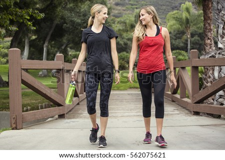 Two attractive women in their 30s talking a walk or jog together in the outdoors. Cute blond and fit women who are active and working to stay healthy.  #562075621