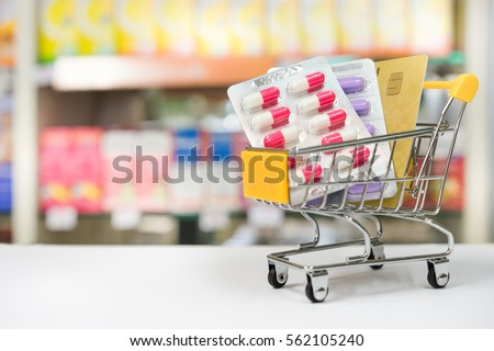 Shopping trolley with blisters of medical capsule pills and credit card with Blurred medicines shelves in pharmacy shop background Royalty-Free Stock Photo #562105240