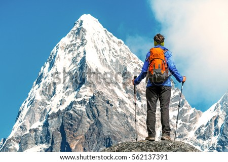 Hiker with backpacks reaches the summit of mountain peak. Success, freedom and happiness, achievement in mountains. Active sport concept. #562137391
