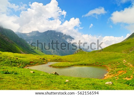 Mountain Lake in the Caucasus summer. Blue sky with white clouds. #562156594