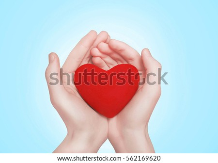 Open hands holding showing red heart over blue background #562169620