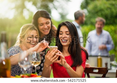 Group of female friends in their thirties having fun while they are watching pictures on a smartphone. In the background a beautiful garden where their men doing a bbq. Shot with flare