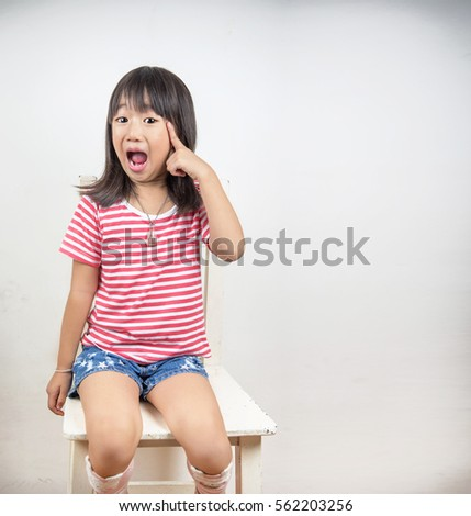 Clever little girl Asian with a bright idea pointing upwards with her finger to gain attention Isolated on white with blank copyspace above her finger #562203256