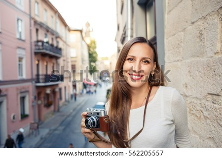 Young cheerful woman standing with camera at the balcony in european town #562205557