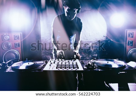 Club DJ playing mixing music on vinyl turntable at party wearing sunglasses with lens flare from nightlife lights. Royalty-Free Stock Photo #562224703