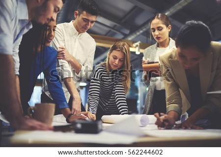 Young male and female architect colleagues drawing graphic planning of interior creation project cooperating with talented teacher giving advice and correcting mistakes during training lesson  Royalty-Free Stock Photo #562244602