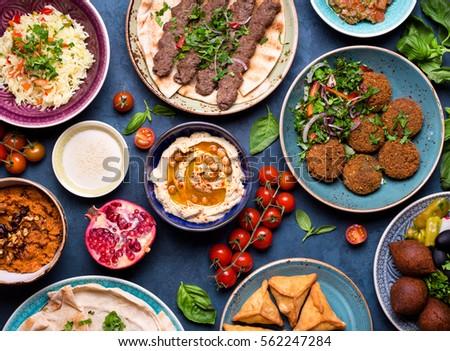 Middle eastern or arabic dishes and assorted meze, concrete rustic background. Meat kebab, falafel, baba ghanoush, muhammara, hummus, sambusak, rice, tahini, kibbeh, pita. Halal food. Lebanese cuisine #562247284