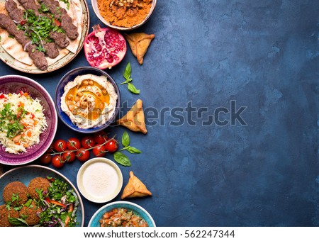 Middle eastern or arabic dishes and assorted meze on concrete rustic background. Meat kebab, falafel, baba ghanoush, hummus, sambusak, rice, tahini, kibbeh, pita. Halal food. Space for text. Top view #562247344