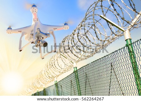 Drone monitoring barbed wire fence on state border or restricted area. Modern technology for security. Digital artwork on industrial theme. #562264267
