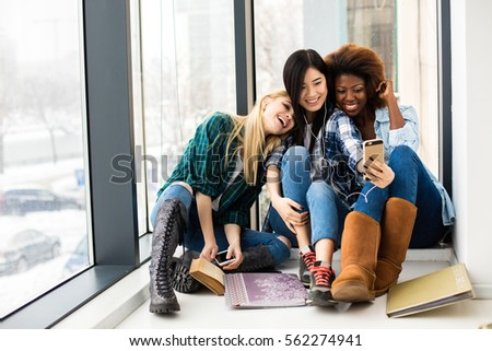 concept of three different ethnic collegue girls, asian, caucasian and afro american, having fun and taking pictures of them selves Royalty-Free Stock Photo #562274941