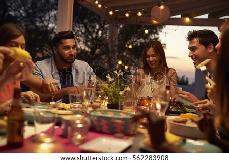 Friends eat and talk at a dinner party on a patio, close up #562283908