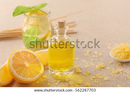 Beautiful spa composition with lemon essential oil on gray background, closeup #562287703
