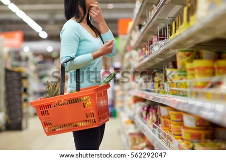 sale, shopping, consumerism and people concept - woman with food basket at grocery store or supermarket Royalty-Free Stock Photo #562292047