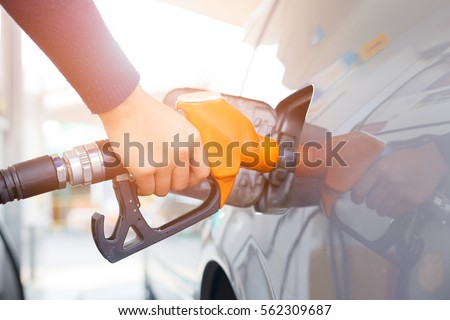 Grey car at gas station being filled with fuel on thailand Royalty-Free Stock Photo #562309687