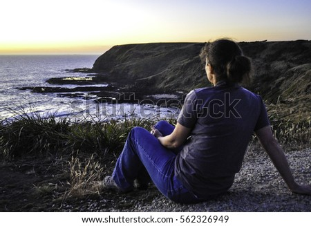 middle aged woman sits alone atop a cliff overlooking the ocean #562326949