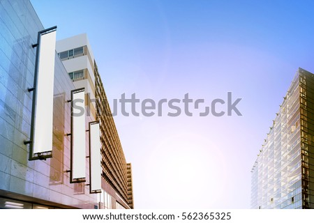 Blank white vertical banners on building facade, design mockup. Store flags mock up on the street. Outdoor bannerets template on the side of the shop exterior. Three signs hanging on the wall.