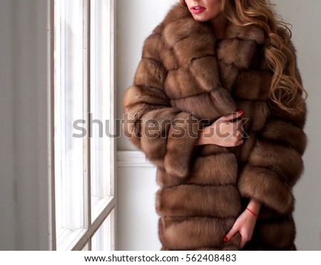 Woman in fur coat, close up, by the window, fur texture #562408483