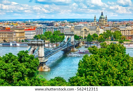 Chain bridge on Danube river in Budapest city. Hungary. Urban landscape panorama with old buildings and domes of opera #562412311