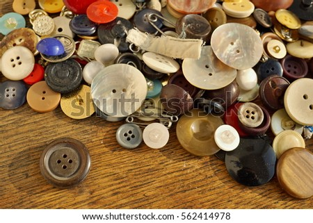 Heap of used worn colorful buttons on the wooden table as a symbolic fashion background  #562414978
