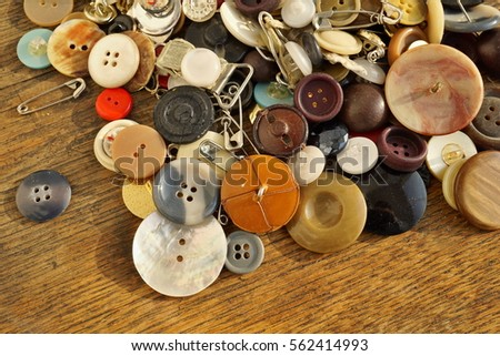 Heap of used worn colorful buttons on the wooden table as a symbolic fashion background  #562414993