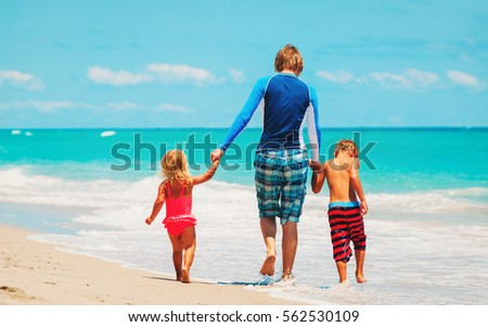 father and two kids walking on beach #562530109