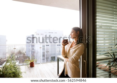 Woman relaxing on balcony holding cup of coffee or tea Royalty-Free Stock Photo #562594846