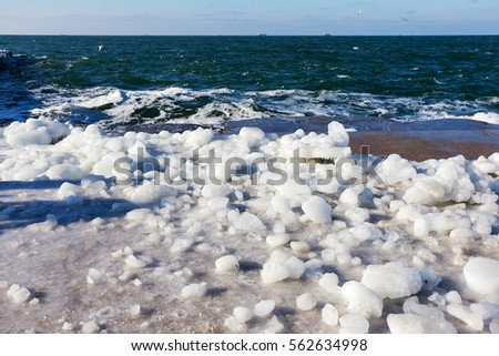 Snow and ice on the sea promenade. Icing seaside promenade after a strong winter storm with heavy frost. #562634998