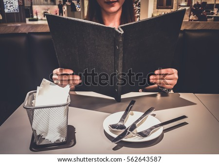 Teenage girl or young woman Choosing Looking from a Restaurant Menu deciding what to order . Breakfast and dinner . Customize colors Vintage retro and old film Tone  #562643587