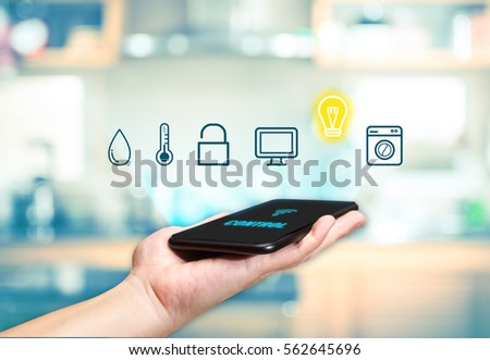 Hand holding mobile with Smart home control icon feature with blur kitchen background,Digital Lifestyle concept #562645696