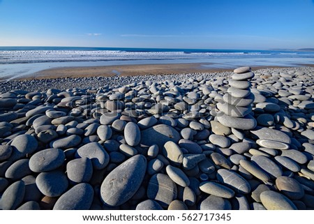 Balanced stones on the Pebble Ridge at Westward Ho! in North Devon, England Royalty-Free Stock Photo #562717345