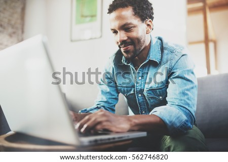Attractive bearded African man spending free time in sofa and using laptop at modern home.Concept of young people enjoying mobile devices.Blurred background. #562746820