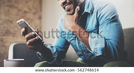 Attractive bearded African businessman using smartphone while sitting on sofa at his home.Concept of young people working mobile devices.Closeup with a selected focus.Blurred background.Wide #562748614