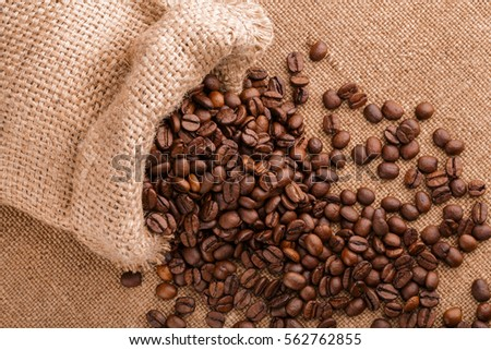 coffee beans on burlap background. roasted coffee beans isolated in white background. Roasted coffee beans background close up. Coffee beans pile from top on white background with copy space for text #562762855