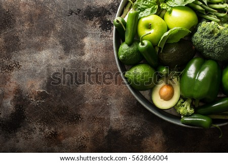 Variety of green vegetables and fruits on a tray, dark setting overhead shot #562866004