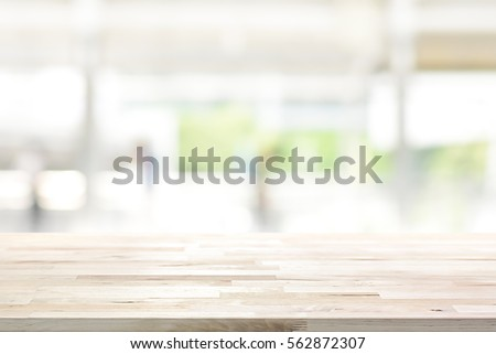 Wood table top on blur kitchen window background - can be used for display or montage your products (or foods) Royalty-Free Stock Photo #562872307