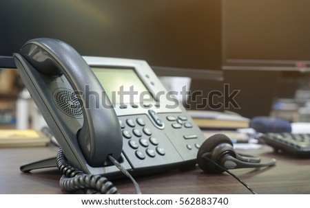 close up soft focus on telephone devices at office desk for customer service support concept Royalty-Free Stock Photo #562883740