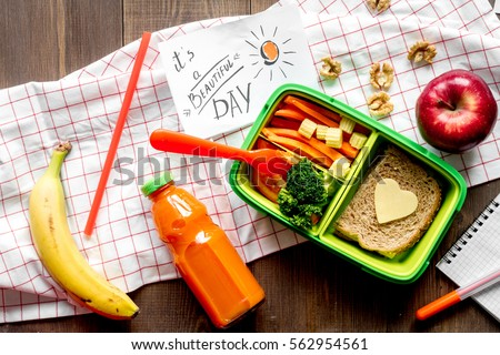 green lunch box for kid on wooden background top view #562954561