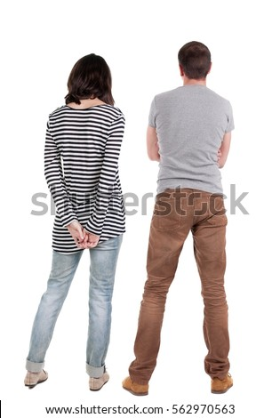 Back view of young couple  hug and look into the distance. beautiful friendly girl and guy together. Rear view. Isolated over white background. young woman holds the hand of her husband looking away #562970563