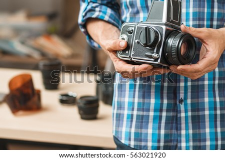 Old professional medium format photo camera close-up. Unrecognizable photographer holding film camera, blurred negatives on background, free space for text