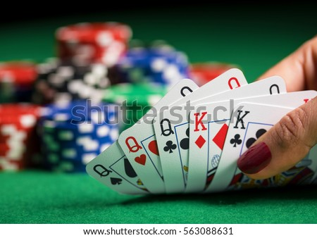 Person playing poker and looking at cards Royalty-Free Stock Photo #563088631