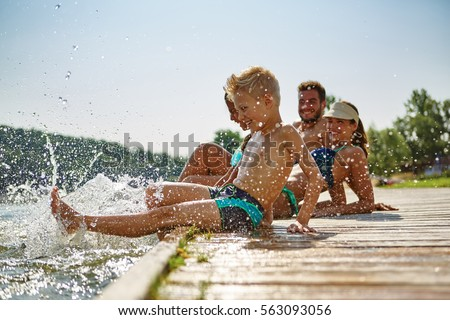 Happy family at a lake having fun and splashing water in summer Royalty-Free Stock Photo #563093056
