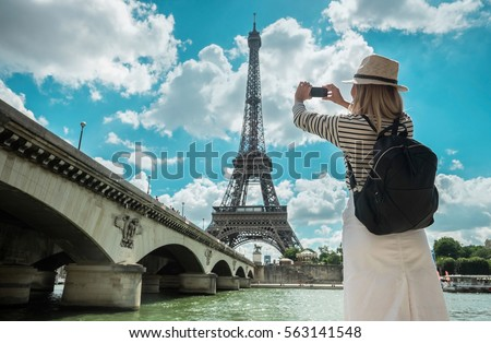 Woman tourist selfie near the Eiffel tower in Paris under sunlight and blue sky. Famous popular touristic place in the world. Royalty-Free Stock Photo #563141548